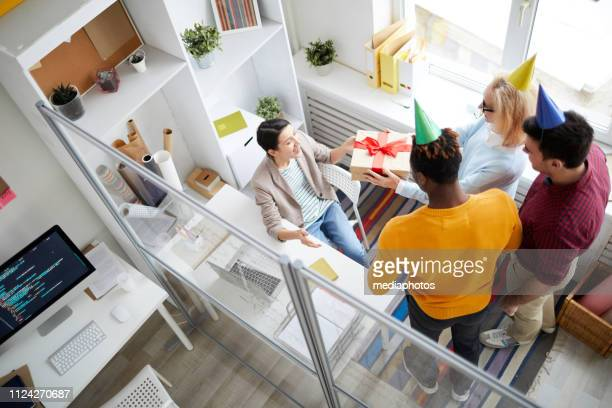 High angle view of multi-ethnic colleagues in party hats giving gift to birthday woman while congratulating her in modern office