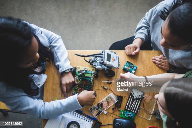 high angle view of multi-ethnic female students preparing science project at desk in high school classroom - stem stock pictures, royalty-free photos & images