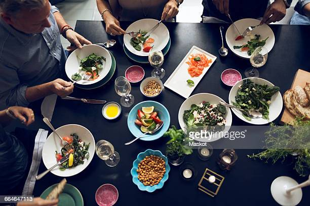 High angle view of multi-ethnic friends eating food at table