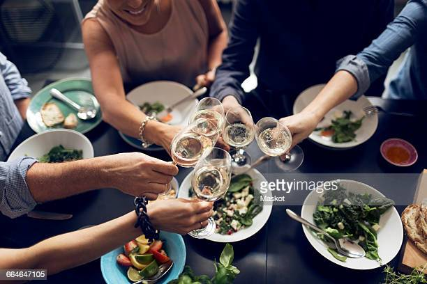 High angle view of multi-ethnic friends toasting wineglasses