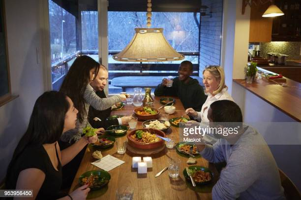 high angle view of multi-generation family enjoying meal at table - medium group of people stock pictures, royalty-free photos & images