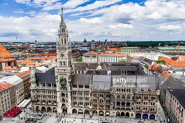 High Angle View Of Munich Cathedral Amidst Buildings Against Cloudy Sky In City