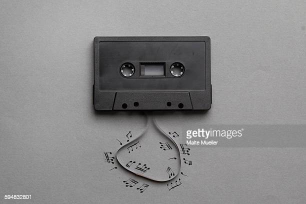 High angle view of music notes drawn around cassette reel on gray background