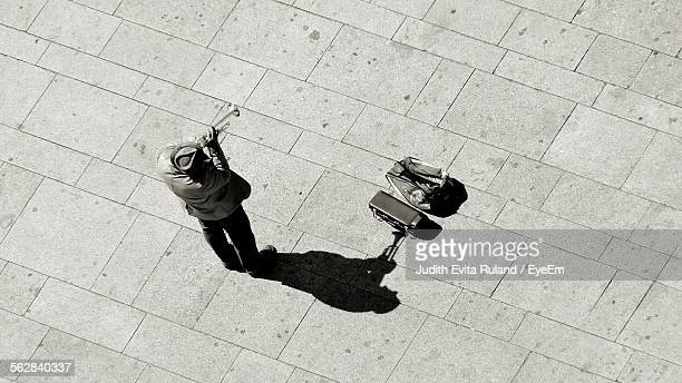 high angle view of musician playing trumpet on street - tromba foto e immagini stock