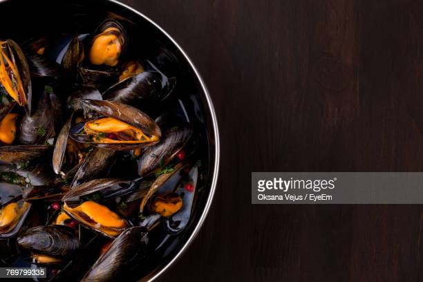 high angle view of mussels in cooking utensil on table - mussel stock pictures, royalty-free photos & images