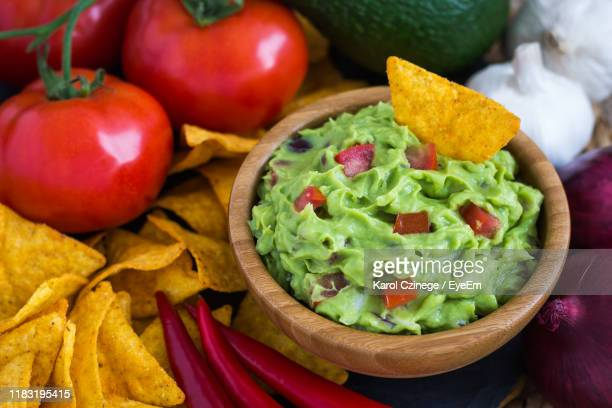 high angle view of nacho chips and guacamole in bowl on table - guacamole stock pictures, royalty-free photos & images