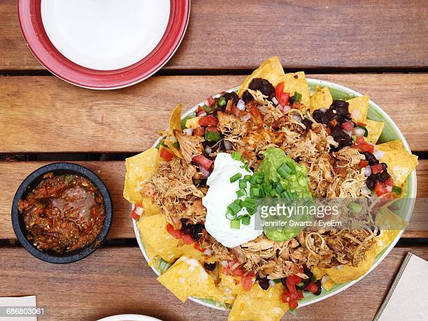 high angle view of nachos with sauce on table - nachos stock photos and pictures