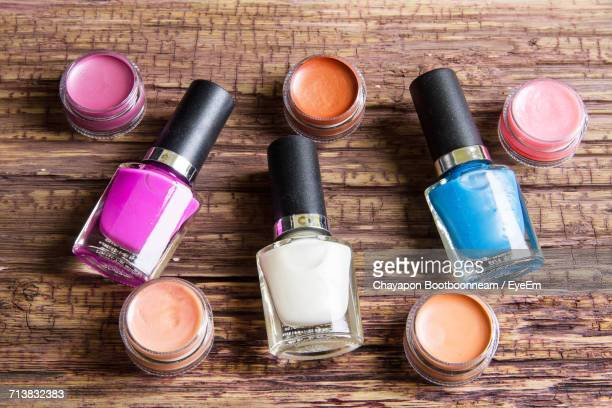 High Angle View Of Nail Polish Bottles With Lip Balm On Wooden Table
