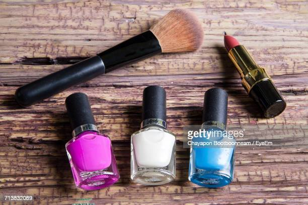 high angle view of nail polish bottles with lipstick and make-up brush on wooden table - white nail polish stock pictures, royalty-free photos & images