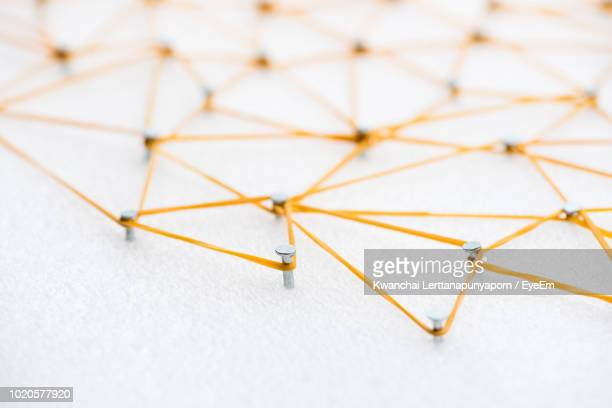 high angle view of nail with rubber band on polystyrene - thread stock pictures, royalty-free photos & images