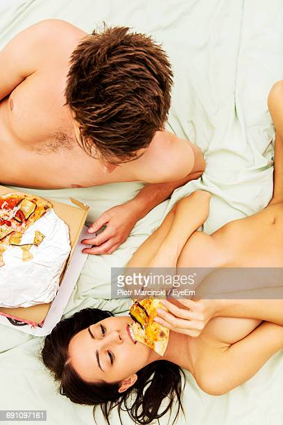 High Angle View Of Naked Couple Eating Pizza On Bed At Home