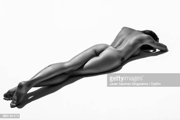 high angle view of naked seductive woman lying on white background - beautiful bare bottoms stock pictures, royalty-free photos & images