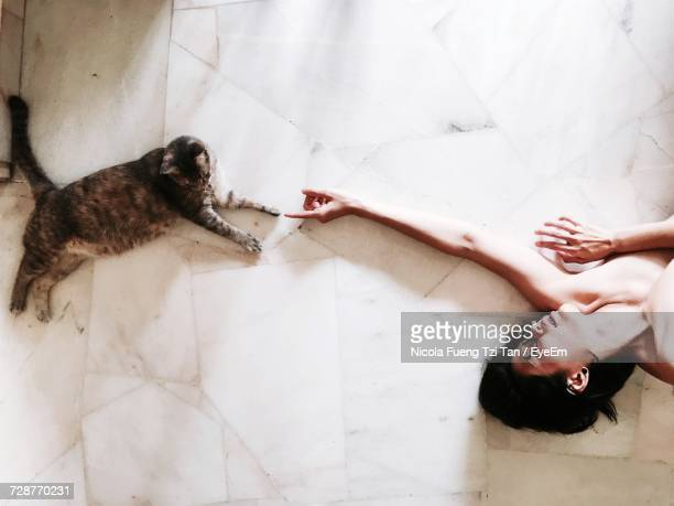 High Angle View Of Naked Woman Lying On Floor While Pointing Towards Tabby Cat At Home