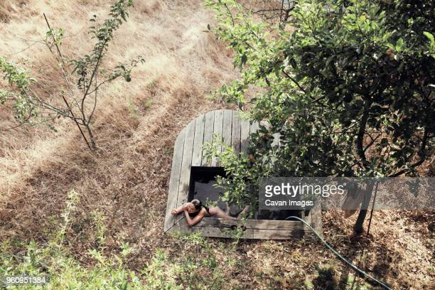 High angle view of naked woman relaxing in hot spring