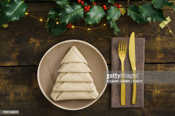 High Angle View Of Napkin In Plate By Cutleries Arranged On Wooden Table