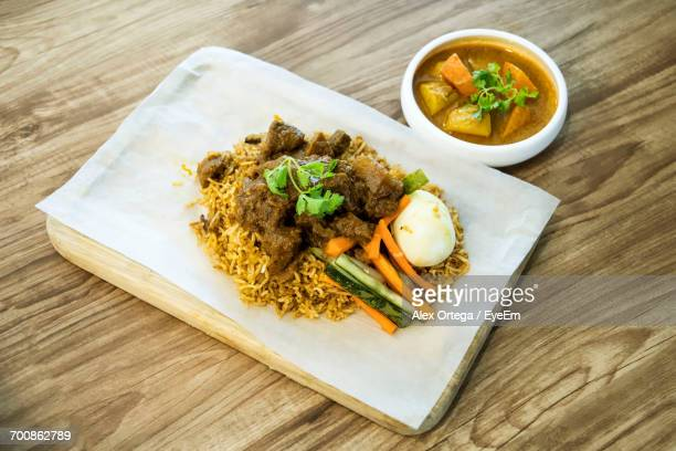 High Angle View Of Nasi Biryani With Rendang Served On Wooden Table