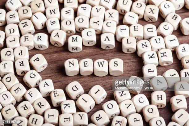 high angle view of news text arranged with alphabet blocks on wooden table - single word stock pictures, royalty-free photos & images