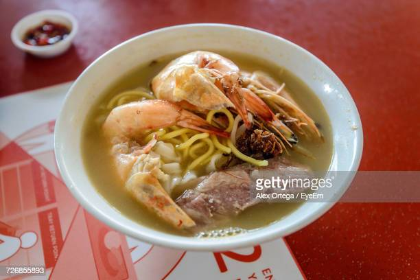 High Angle View Of Noodle Soup With Prawns Served In Bowl On Red Table