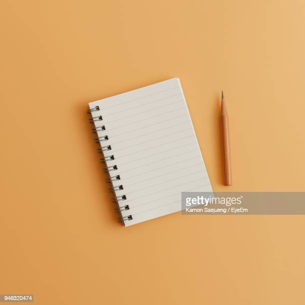 high angle view of note pad with pencil on brown background - notizbuch stock-fotos und bilder