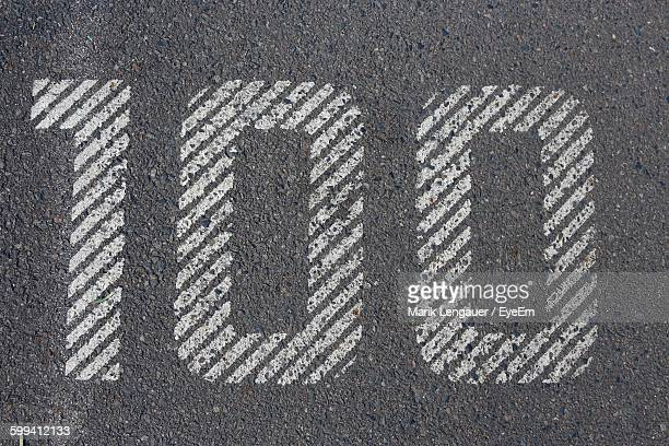 High Angle View Of Number 100 On Road