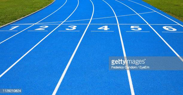 high angle view of numbers on blue running track - track and field stadium stock pictures, royalty-free photos & images