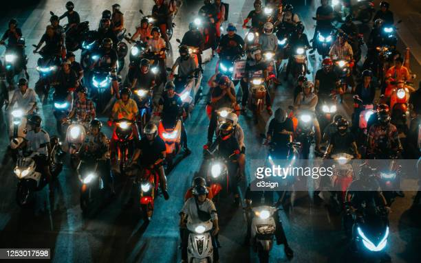 high angle view of numerous illuminated motorbikes in traffic jam with busy city traffic at the red light in downtown, bangkok at night - luchtvervuiling stockfoto's en -beelden