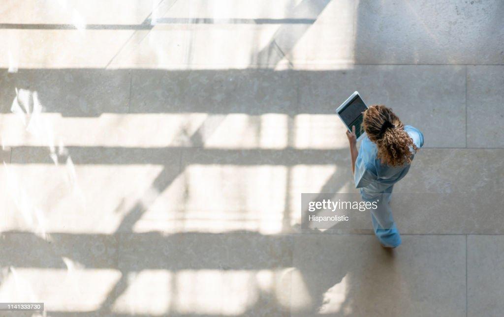 High Angle view van verpleegkundige lopen rond het ziekenhuis, terwijl het kijken naar een medische grafiek op Tablet : Stockfoto