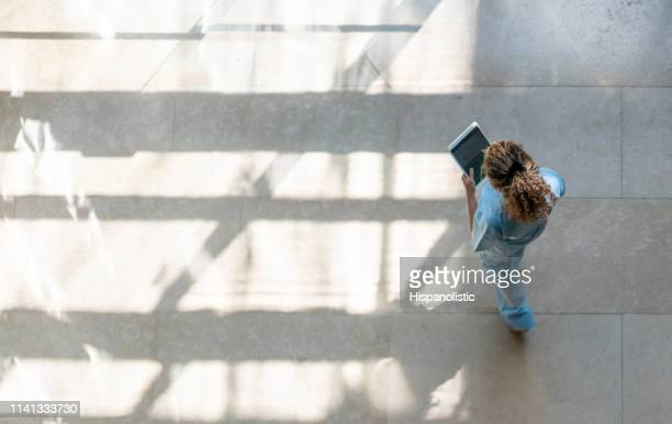 high angle view of nurse walking around hospital while looking at a medical chart on tablet - cuidados de saúde e medicina imagens e fotografias de stock