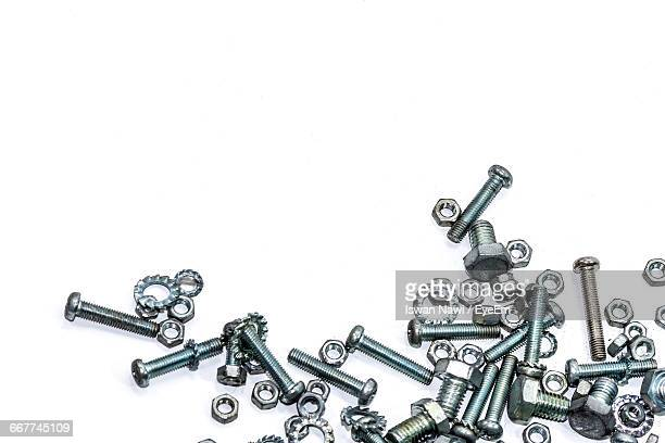 high angle view of nuts and bolts on white background - nut fastener stock photos and pictures