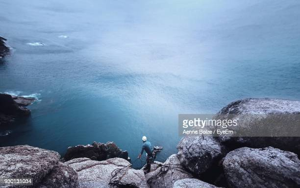 high angle view of of man rock climbing by sea - free climbing stock pictures, royalty-free photos & images