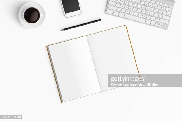 high angle view of office supplies on table - open book stock photos and pictures