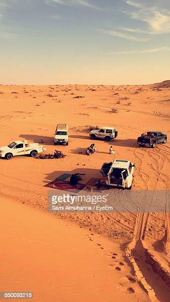 High Angle View Of Off-Road Vehicles And People On Desert Land