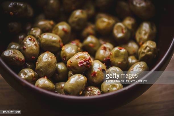 high angle view of olives in bowl on table, ogre, latvia - green olive fruit stock pictures, royalty-free photos & images