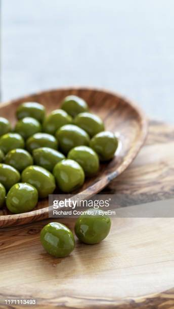 high angle view of olives on table - green olive fruit stock pictures, royalty-free photos & images