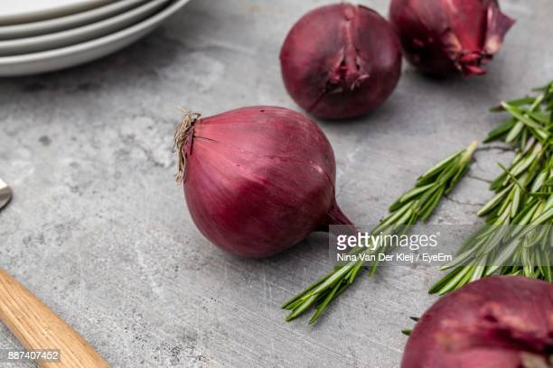 High Angle View Of Onions And Rosemary On Table