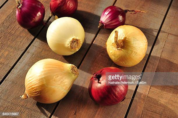 high angle view of onions on wooden table - nathalie pellenkoft stock pictures, royalty-free photos & images