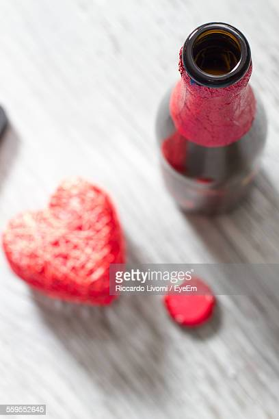 High Angle View Of Open Beer Bottle By Heart On Plank