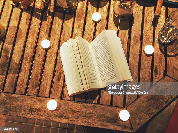 High Angle View Of Open Book Amidst Tea Light Candles On Wooden Table