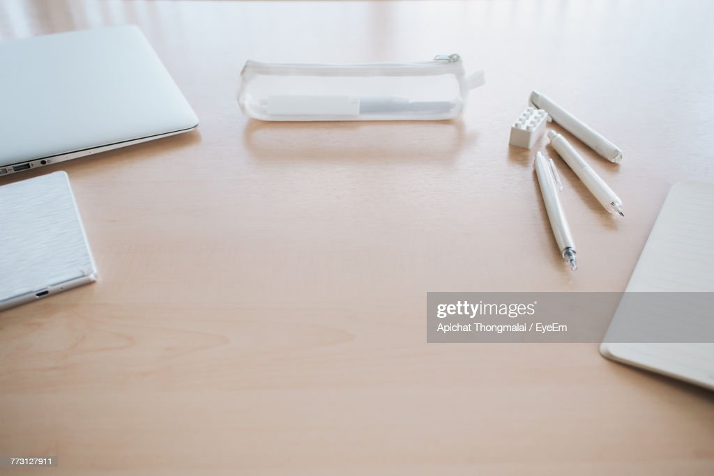 High Angle View Of Open Book By Pen And Mobile Phone On Table : Photo