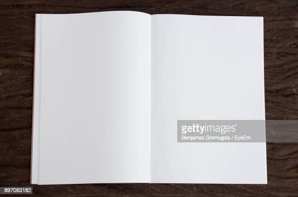 high angle view of open book on table - open book stock photos and pictures