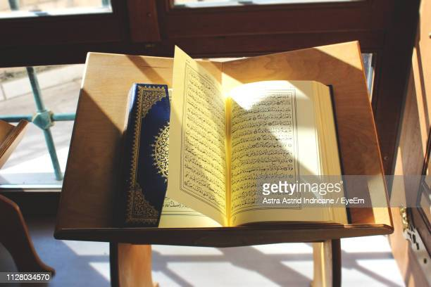 high angle view of open koran on table - allah photos et images de collection