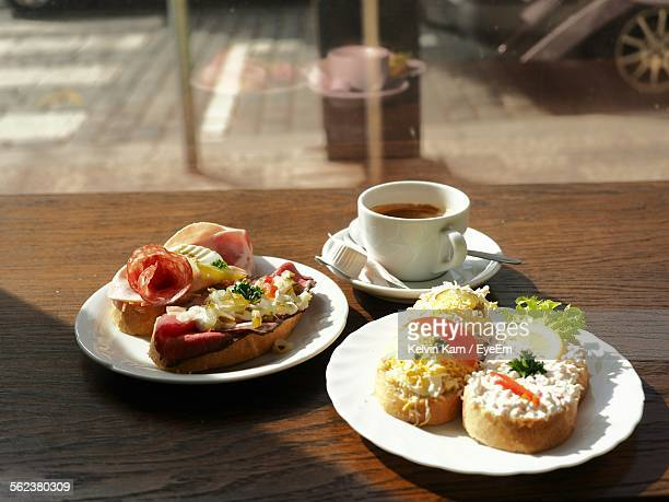 High Angle View Of Open Sandwiches On Plate With Espresso Coffee Cup On Table