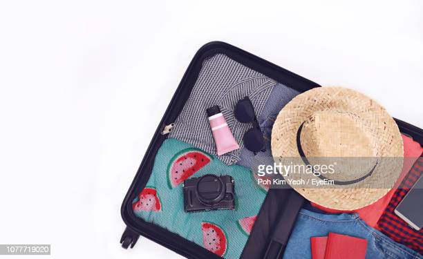 high angle view of open suitcase against white background - straw hat stock pictures, royalty-free photos & images