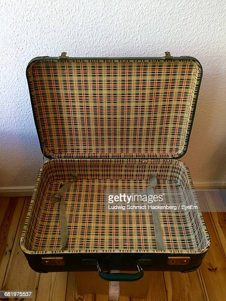 High Angle View Of Open Suitcase On Stool By Wall