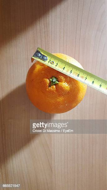 High Angle View Of Orange And Tape Measure On Table