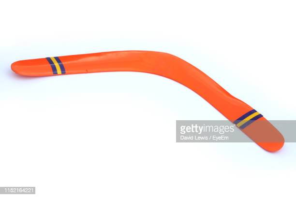 high angle view of orange boomerang on white background - boomerang stock pictures, royalty-free photos & images