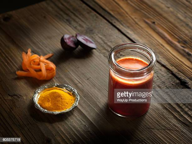 High angle view of orange raw juice in a jar with beetroot, turmeric and grated carrot on wood grain pattern background