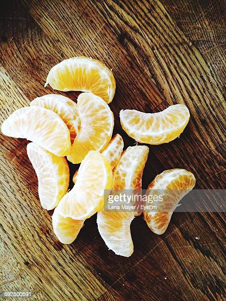 High Angle View Of Orange Slice On Wooden Table