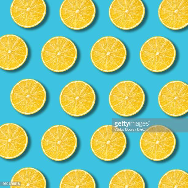 high angle view of orange slices on blue background - zitrone stock-fotos und bilder