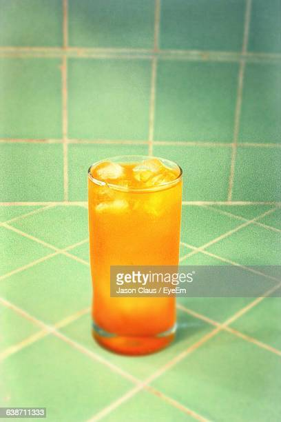 High Angle View Of Orange Soda On Tiled Surface